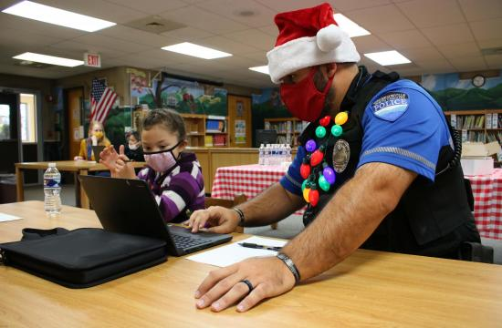 officer in santa hat and student at computer