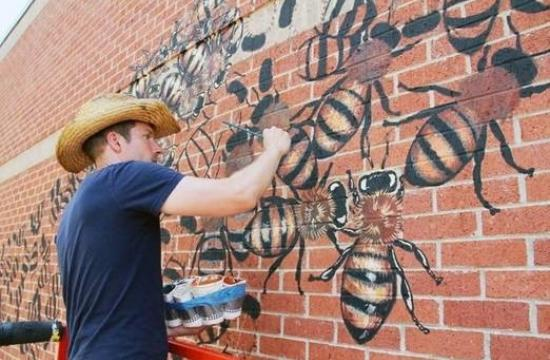 muralist painting bees on a brick wall