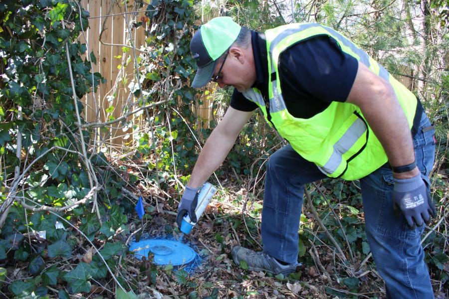crew member spraypainting a water meter