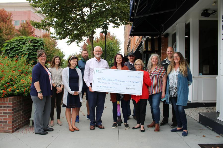 Image of city staff and volunteers with large check from duke energy for $25,000