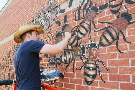 man painting bee mural