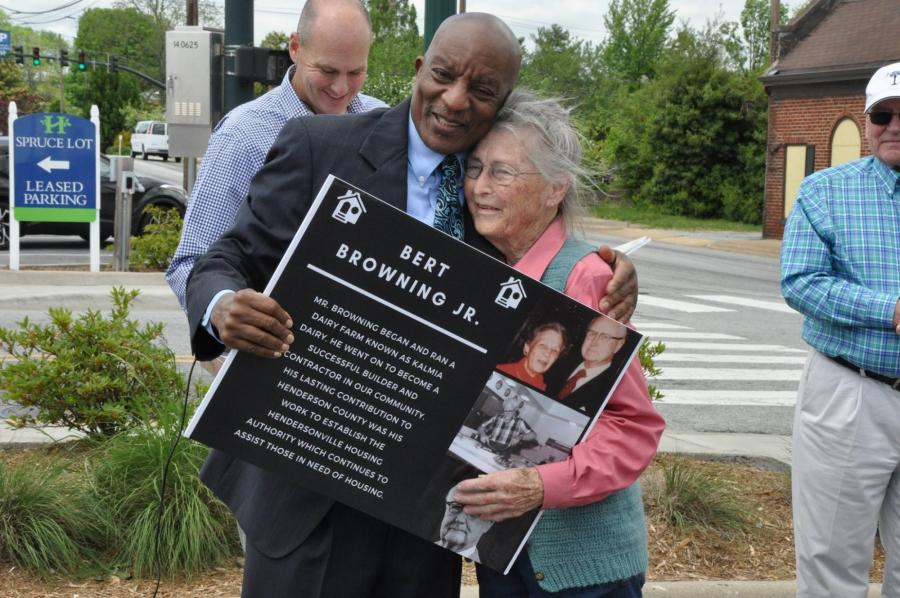 man hugging a woman holding an award