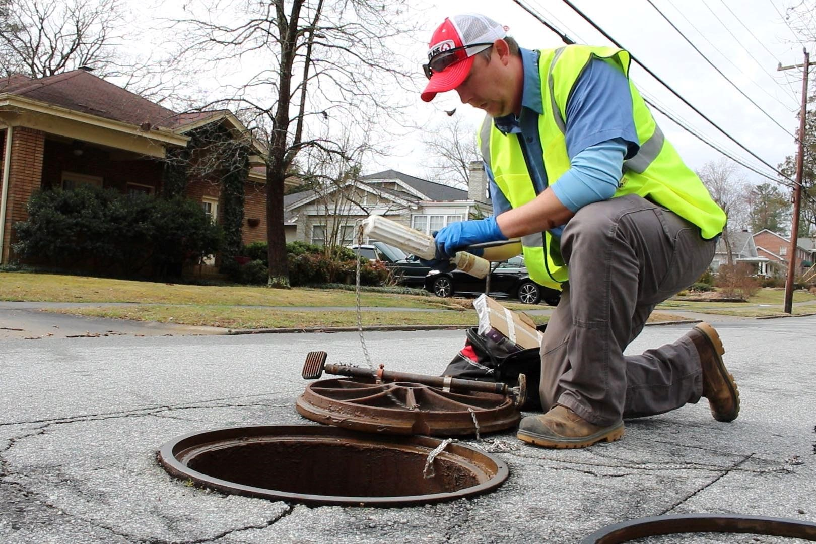 City staff install sewer flow tracking device