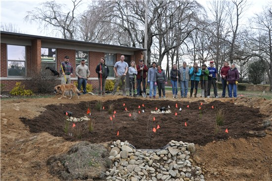 Photo of Bruce Drysdale Elementary rain garden design and construction team and partners standing in front of newly installed rain garden